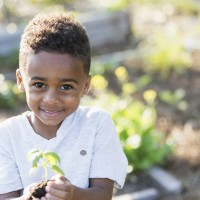 little boy holding a flower for earth day