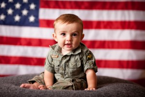 military baby sitting in front of american flag