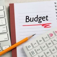 A notebook and calculator being used to create a budget.